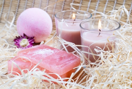Spa items on a straw fabric: candles, natural soap, fizzy bath bombs, straw and flower